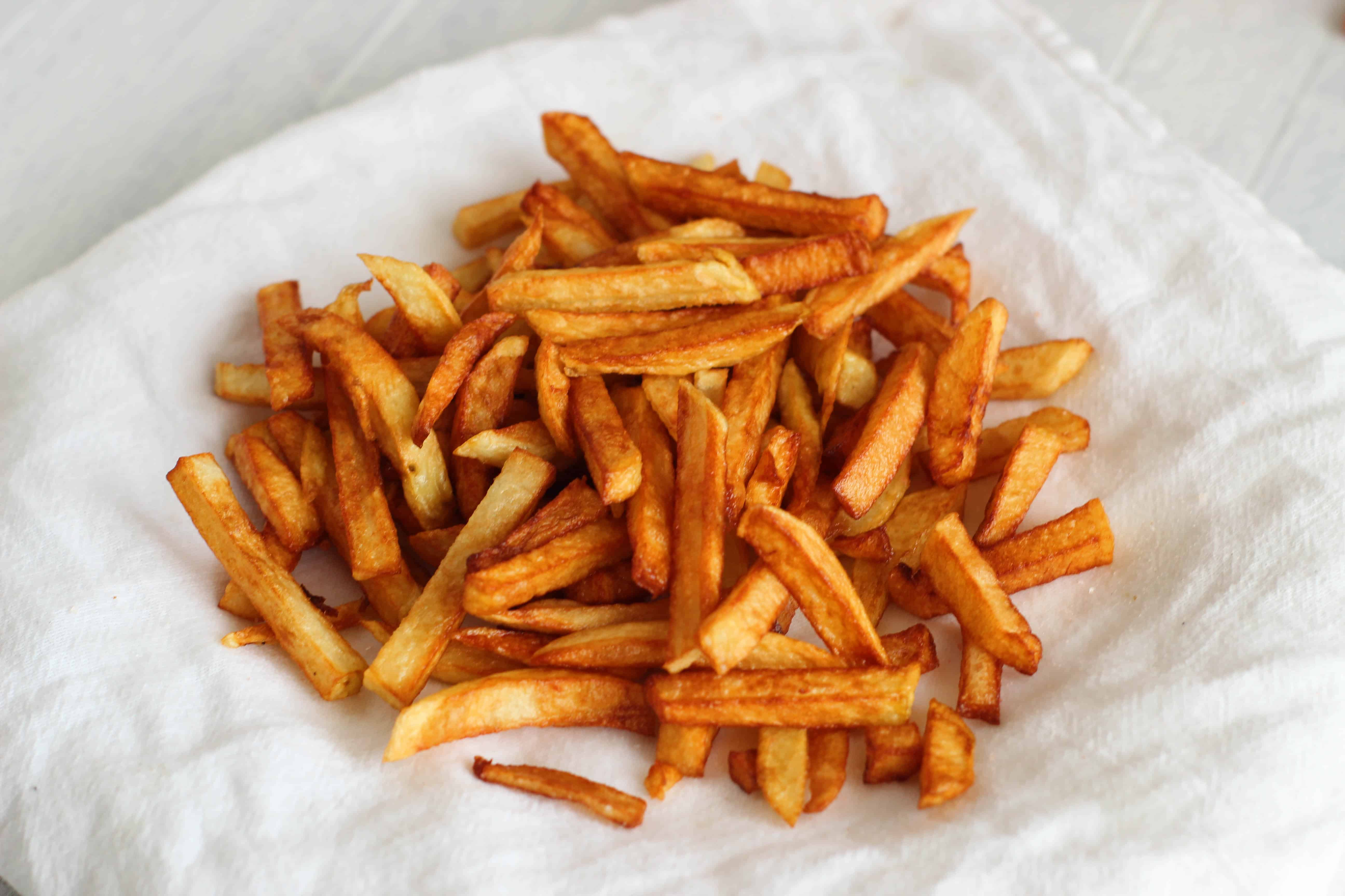 Crispy French fries on white towel.
